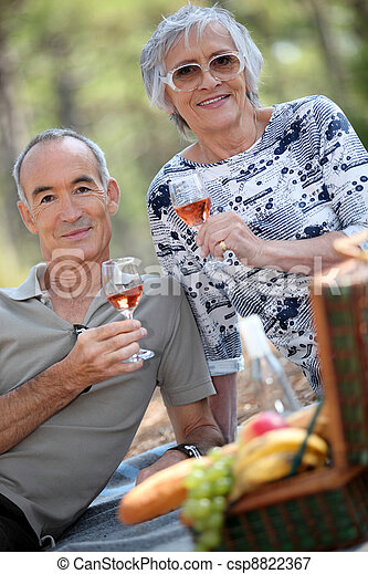 Older couple drinking rose wine with a picnic - csp8822367
