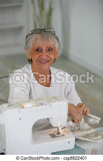 Elderly lady using sewing machine - csp8822401