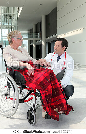 Doctor talking to an elderly woman in a wheelchair - csp8822741