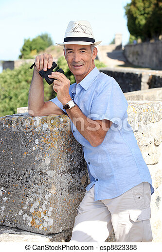 Senior man at a citadel with a pair of binoculars - csp8823388