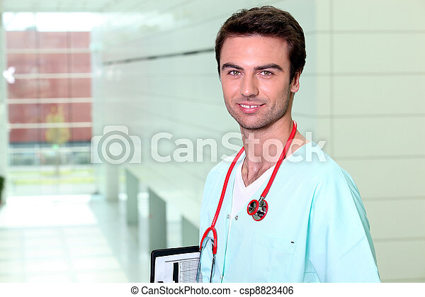 Smiling male nurse alone in a corridor - csp8823406