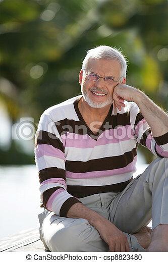 Elderly man sat in garden - csp8823480