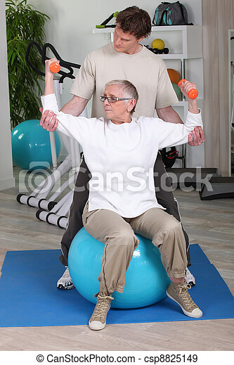 Elderly woman with personal trainer - csp8825149