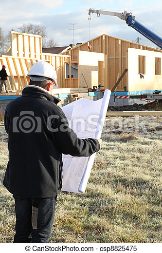construction site supervisor looking at a blueprint - csp8825475