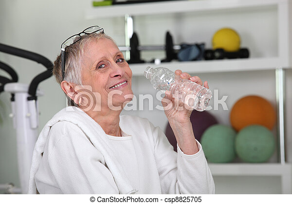 Elderly woman drinking bottled water at a gym - csp8825705