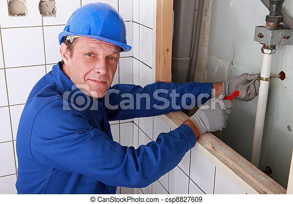 Plumber fixing water supply in bathroom - csp8827609