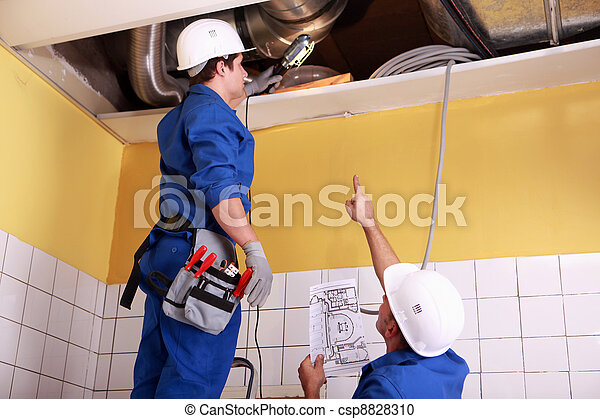 two technicians checking the air conditioning in the ceiling - csp8828310