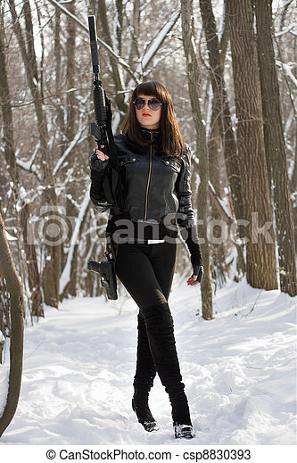 Pretty woman in black with weapon - csp8830393