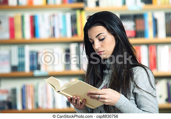 female student reading a book in library - csp8830756