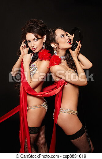 fashion portrait of two sexy brunette girls in light lingerie with long curly hair and jewellery bright makeup red lips with red ribbon isolated on black with headphones - csp8831619