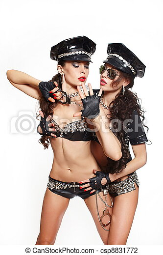 two sexy beautiful  brunette semi nude police women with long curly hair with handcuffs with glasses with birght makeup and red lips one girl arresting another - csp8831772