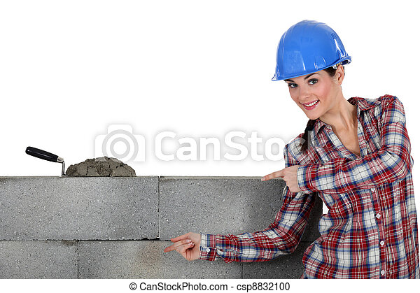 A female mason showing her work. - csp8832100