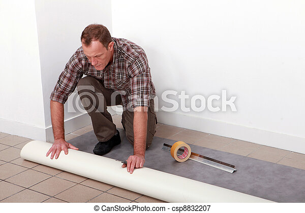 Man unrolling carpet - csp8832207