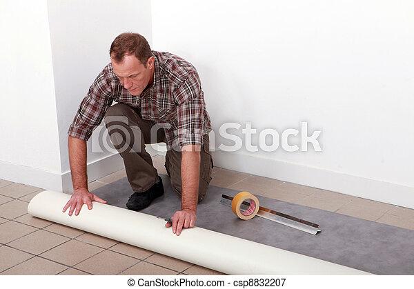 Man unrolling carpet - csp8832207