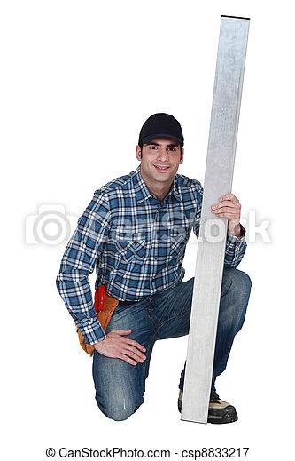 Man holding sheet of metal - csp8833217