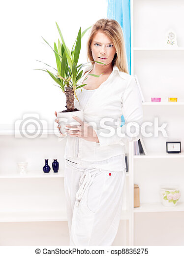 woman holding plant in pot at home - csp8835275