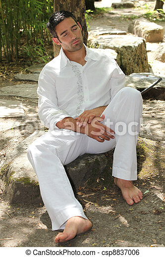 30 years old man sleeping and leaning against a tree - csp8837006