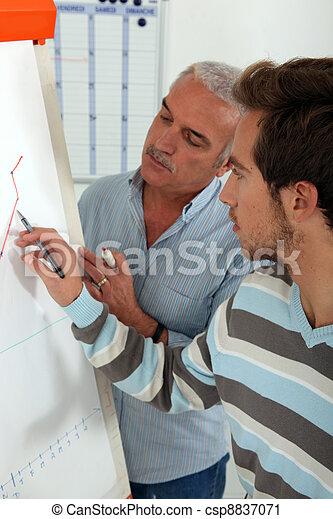 Men writing statistics on paperboard - csp8837071