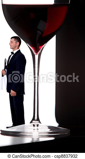 wine steward posing next to giant glass of wine - csp8837932