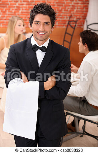 well dressed waiter facing the camera, behind a couple is dining at restaurant - csp8838328