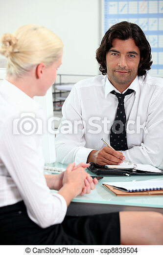 Office colleagues talking at a desk - csp8839504