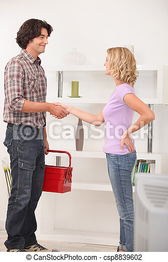 A maintenance man shaking hand with the homeowner. - csp8839602