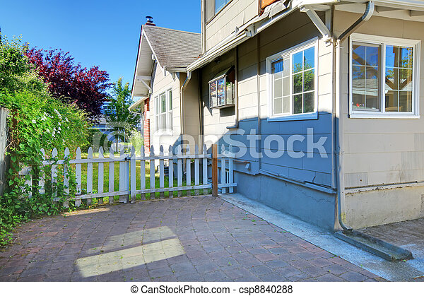 Cute grey house exterior with patio and small fence - csp8840288