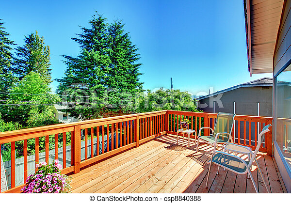 Large new wood deck home exterior with chairs. - csp8840388