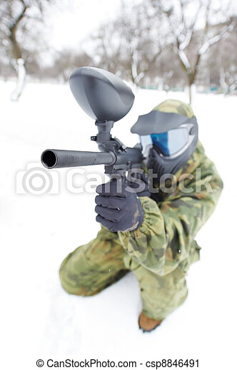 paintball player with marker at winter outdoors - csp8846491