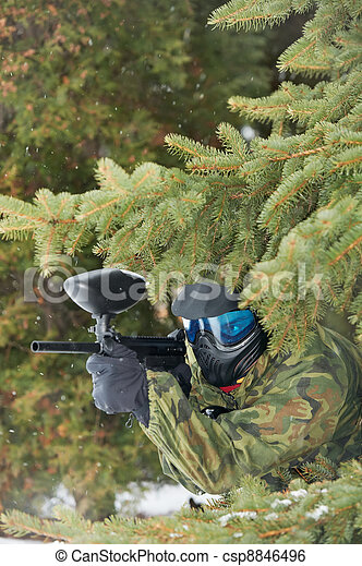 paintball player with marker at winter outdoors - csp8846496