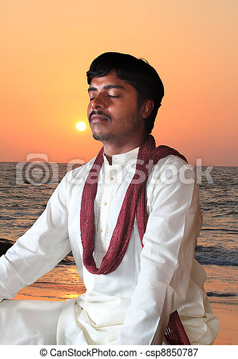 Young indian man in meditation posture at beach - csp8850787