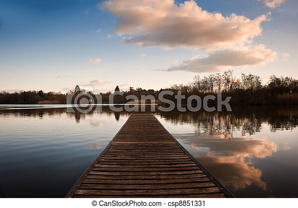 Beautiful late evening sunset landscape over jetty on lake - csp8851331
