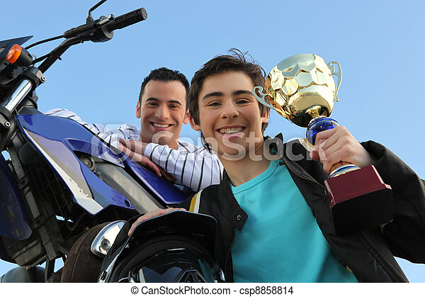father and son holding trophy after motorbike race