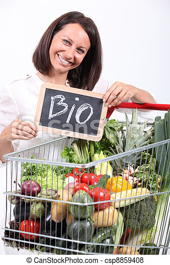 Woman with a trolley of organic vegetables - csp8859408