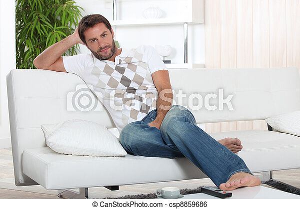 A man resting on his sofa. - csp8859686
