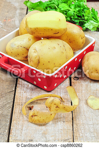 Raw potatoes in red tray and potato peels - csp8860262