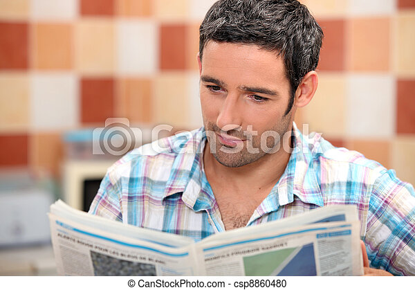 Man reading a journal in the kitchen - csp8860480