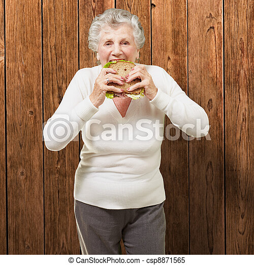 portrait of senior woman eating vegetal sandwich against a wooden wall - csp8871565