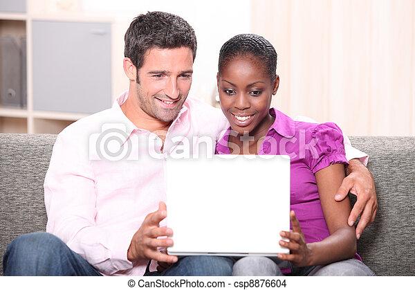 Couple sat on sofa watching laptop screen