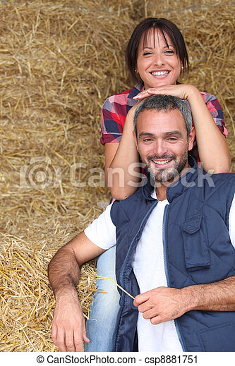 Farmer couple sitting amongst hay bales - csp8881751