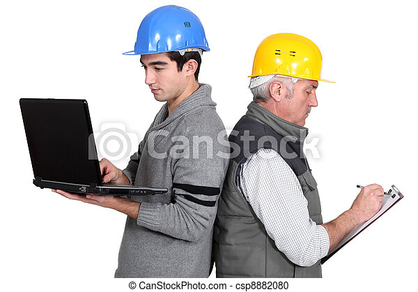 Builder and apprentice with laptop and clipboard - csp8882080