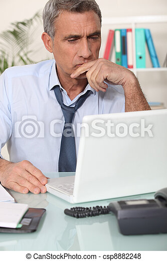 Grouchy man reading an email - csp8882248