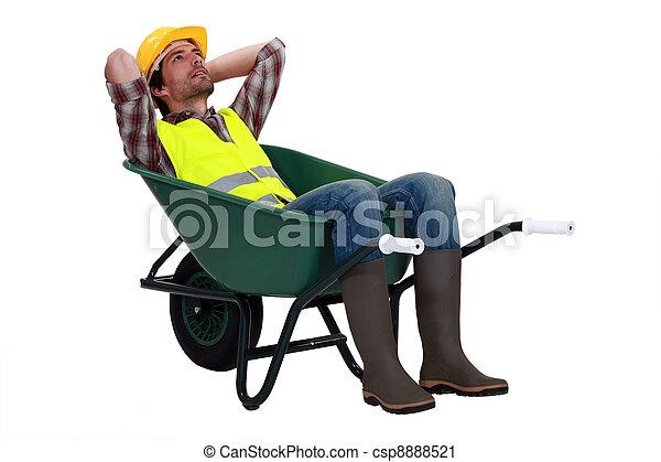 Construction worker resting in a wheelbarrow - csp8888521