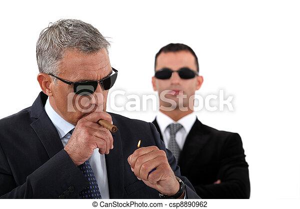 Wealthy businessman smoking cigar - csp8890962