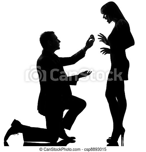 one caucasian couple man kneeling offering engagement ring and woman happy surprised in studio silhouette isolated on white background - csp8893015