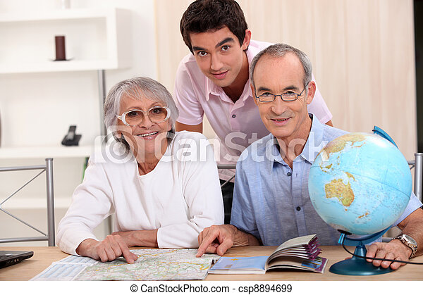 Young man and senior couple seeking a route on a map - csp8894699