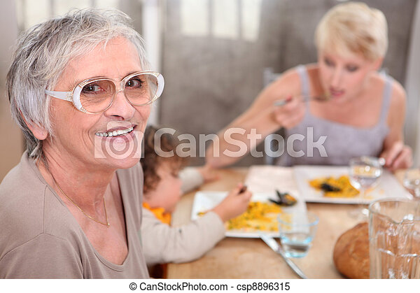 Grandma joins an informal family supper - csp8896315