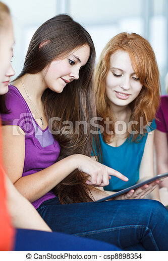 Young college students using a tablet computer in class  - csp8898354