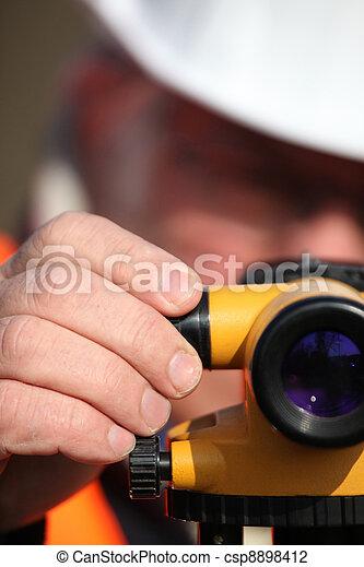 Civil engineer adjusting a theodolite - csp8898412