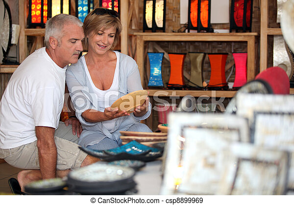 Couple looking at local pottery on holiday - csp8899969